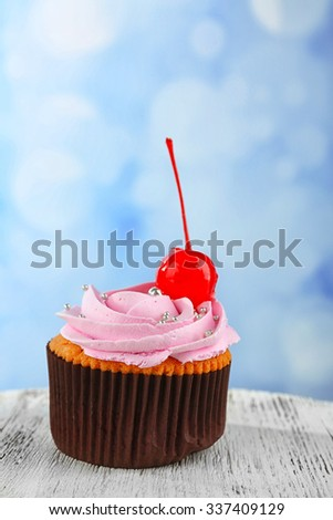 Tasty cupcake on color wooden table, on bright background - stock photo