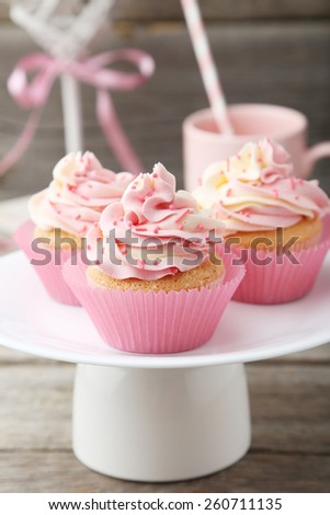 Tasty cupcake on grey wooden background - stock photo