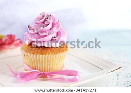 Tasty cupcake on plate, on light background - stock photo
