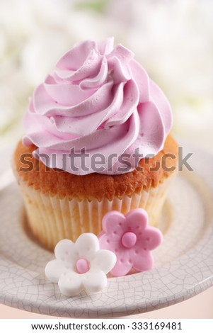 Tasty cupcake on stand, on light background - stock photo