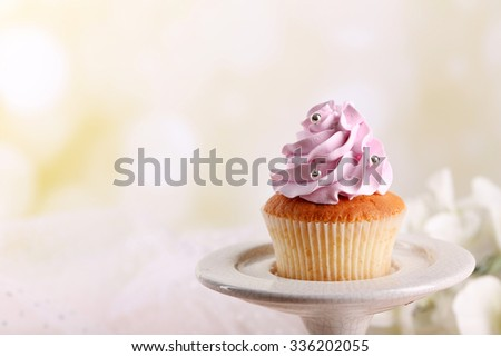 Tasty cupcake on stand, on light background