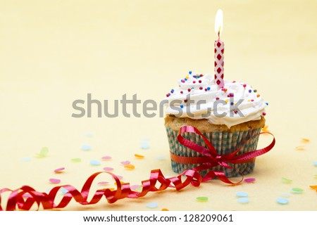 Tasty cupcake with a ribbon and a lit candle. - stock photo