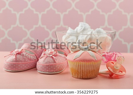 Tasty cupcake with bow and baby shoes, pacifier on color background