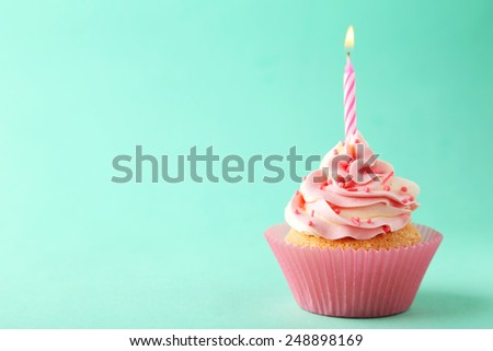 Tasty cupcake with candle on green background - stock photo