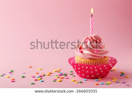 Tasty cupcake with candle on pink background - stock photo
