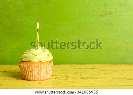 Tasty cupcake with candle on yellow wooden table against green background - stock photo