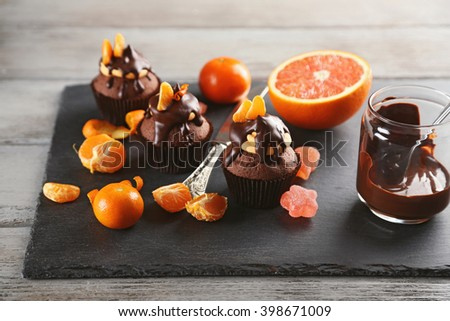 Tasty cupcake with fruits, chocolate and knife on slate plate over white wooden background - stock photo