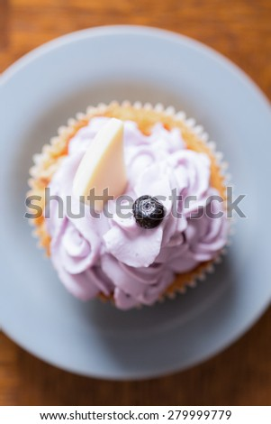 Tasty cupcake with mascaropne and blueberry and chocolate on top - stock photo