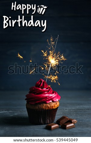 Tasty cupcake with sparkler on table. Text HAPPY BIRTHDAY on background