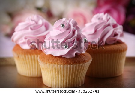 Tasty cupcakes on bright background - stock photo