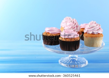 Tasty cupcakes on color wooden background - stock photo