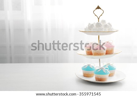 Tasty cupcakes on stand, on light background - stock photo