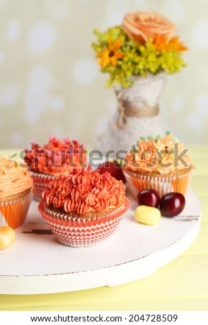 Tasty cupcakes on table, on bright background - stock photo