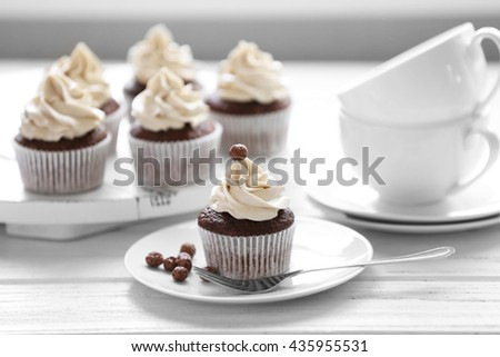 Tasty cupcakes on wooden table