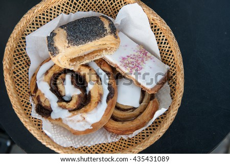 Tasty Danish pastry and cakes in a basket, on a table, stock picture