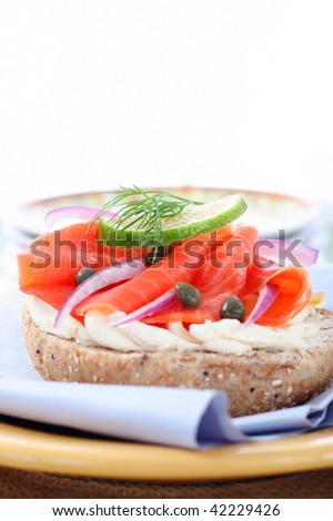 tasty deli lunch, wholegrain bagel with smoked salmon, narrow focus - stock photo