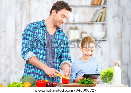 Tasty dinner. Pleasant handsome smiling father cutting vegetables while cooking together with his daughter in the kitchen - stock photo