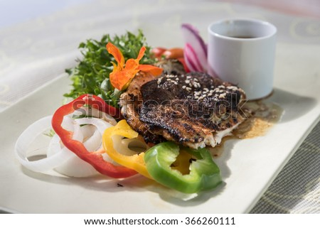 Tasty dish of rainbow trout steak with sesame oil sauce and fresh vegetables.