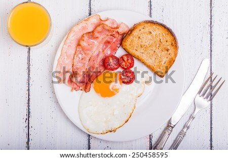 Tasty dish with the traditional bacon and eggs served with toast - stock photo