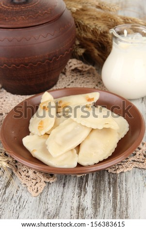 Tasty dumplings with fried onion on brown plate, on wooden background
