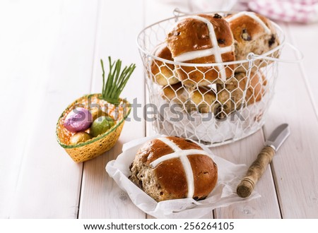 Tasty Easter cross-buns served on a white wire metal basket on white wooden background - stock photo