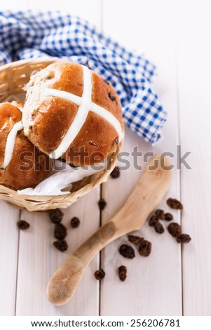 Tasty Easter cross-buns served on a woven basket, eco wooden knife and raisins on white wooden background. Selective focus, shallow depth of field - stock photo