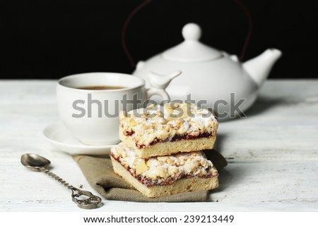Tasty eclairs and cup of tea on wooden table, on black background - stock photo