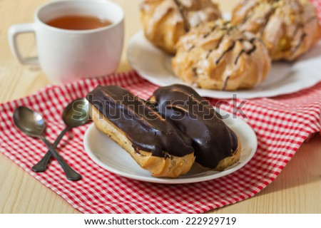 Tasty eclairs on table with tea cup - stock photo