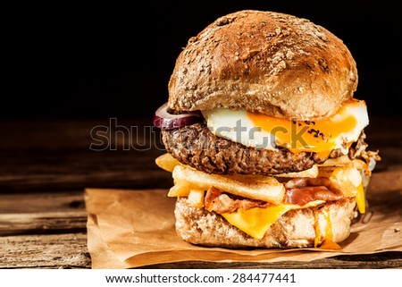 Tasty egg and bacon cheeseburger with a ground beef patty, fried egg, cheese, french fries, onion and bacon served on a fresh roll on brown paper with copyspace - stock photo
