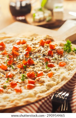 Tasty Elsass Alsace pizza on a thin crispy base flame grilled in a pizzeria and topped with mozzarella cheese, herbs, onions and ham served on a wooden board - stock photo