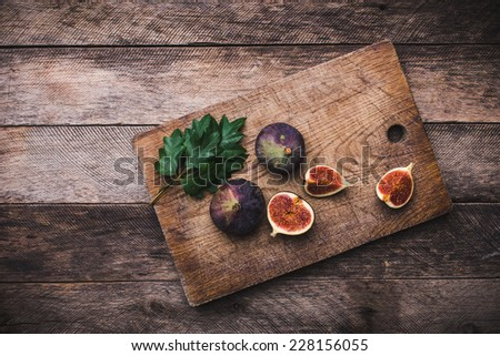Tasty Figs on chopping board and wooden table. Autumn season food photo - stock photo