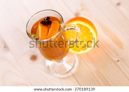 Tasty fragrant warming drink grog with rum, lemon and fruit in a glass on the table of the cafeteria. Hot Citrus alcoholic cocktail. - stock photo
