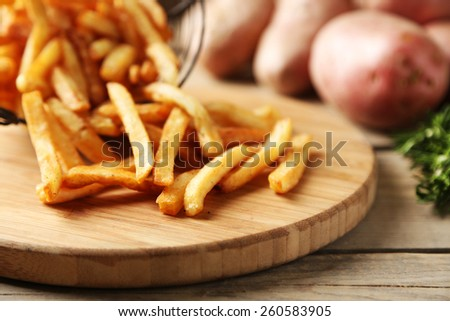 Tasty french fries in metal basket on wooden table background - stock photo