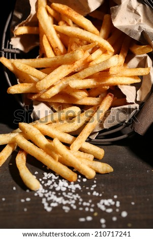 Tasty french fries in metal basket on wooden table with dark light - stock photo