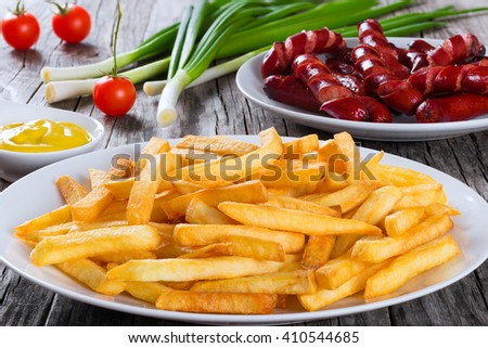 Tasty french fries on a plate and delicious grilled sausages on a white dish on wooden table background, close up - stock photo