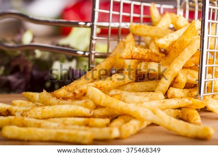 Tasty french fries on cutting board, on wooden table background - stock photo