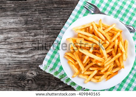 Tasty french fries on white plate on table napkin with fork, on wooden background, blank space left, top view - stock photo