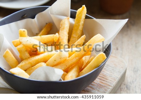 tasty french fries on wooden table background - stock photo