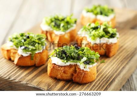 Tasty fresh bruschetta on cutting board on grey wooden background - stock photo