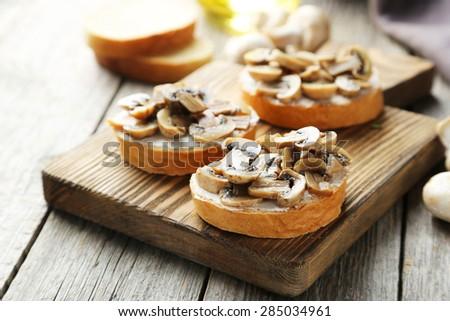 Tasty fresh bruschetta with mushrooms on cutting board on grey wooden background - stock photo