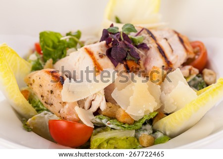 tasty fresh caesar salad with grilled chicken parmesan and croutons - stock photo