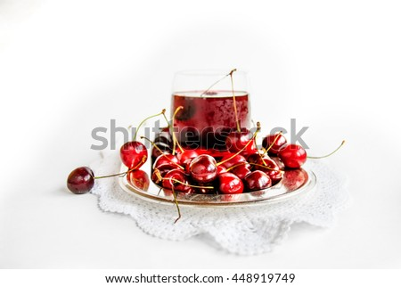 Tasty fresh cherry and cherry juice on metal plate with laced napkin, on white background, selective focus (closeup) - stock photo