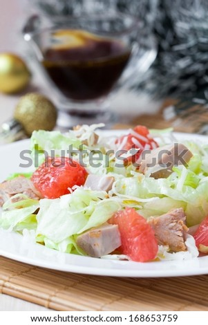 Tasty fresh salad with grapefruit, chicken, lettuce, cheese and sauce, Christmas appetizer - stock photo