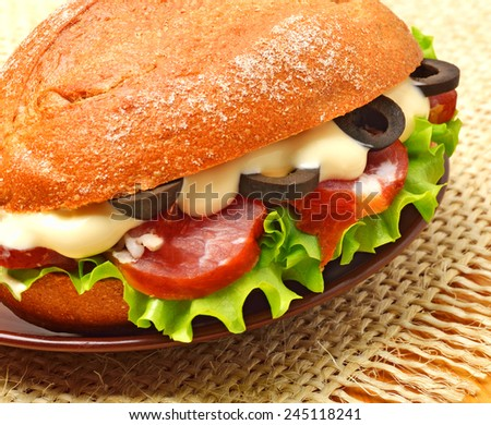 Tasty fresh sandwich with green lettuce, ham and olives on the sacking background - stock photo
