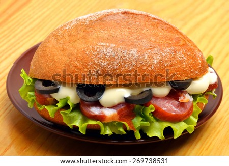 Tasty fresh sandwich with green lettuce, ham and olives on the wooden background - stock photo