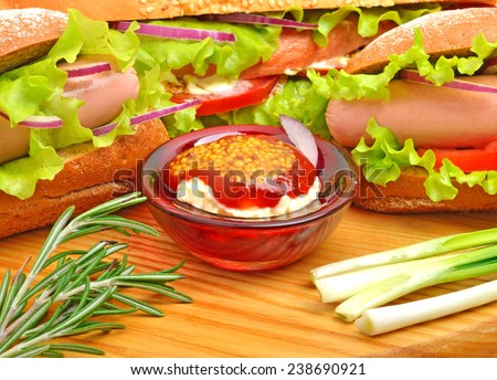 Tasty fresh sandwiches with green lettuce, ham, green onion and sauce on cutting board - stock photo
