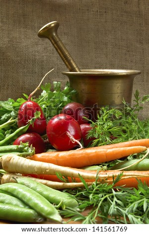 Tasty fresh vegetable with old bronze mortar. - stock photo