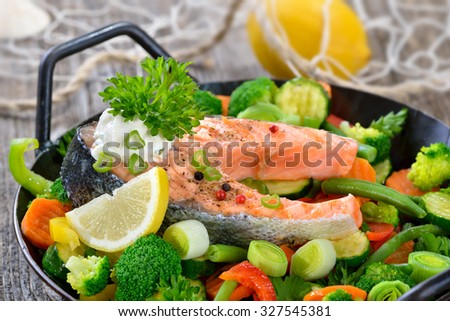 Tasty fried and grilled salmon steak on mixed colorful vegetables served in a frying pan,  lemons and a fishing net in the background - stock photo
