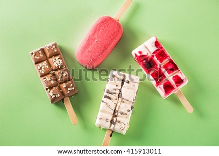Tasty frozen ice cream with different tastes on green background - stock photo