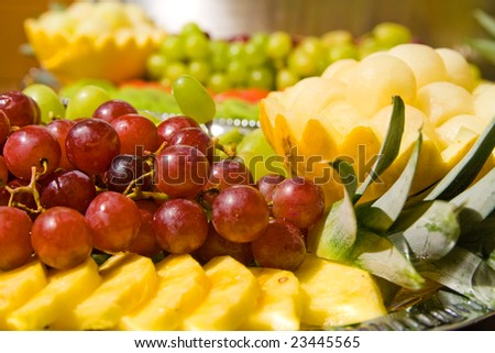 Tasty fruit salad on tray. Multiple fruits.